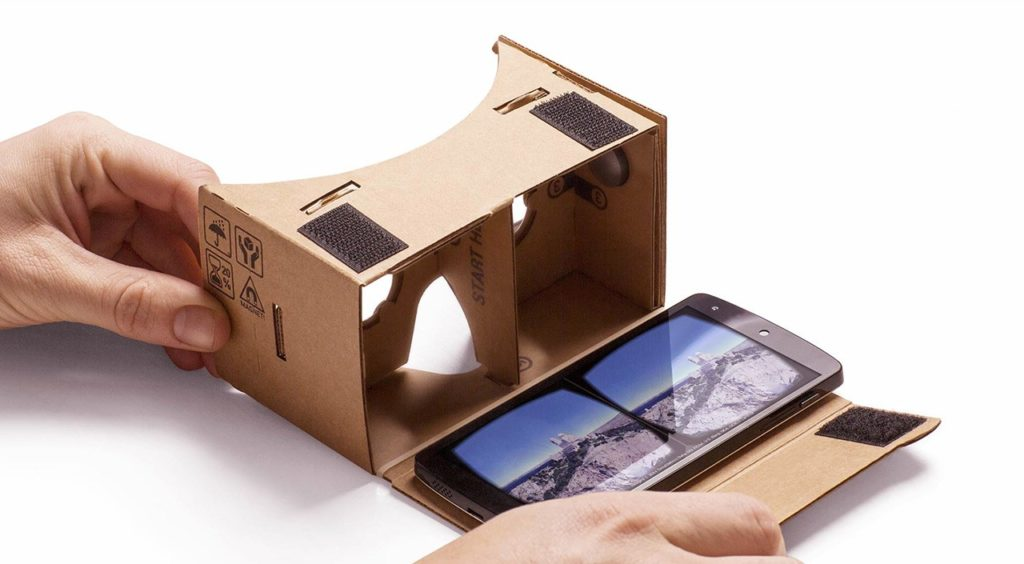 close up of hands opening Google Cardboard with phone inside with mountains on screen