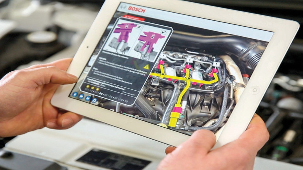 BOSCH AR Used For Business Employee Training, close up of i-pad held over some motor parts with AR information displaying on screen