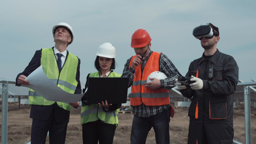 Corporate VR Training For Employees - 4 People On A Construction Site, 2 man and 1 woman with helmets, holding a map, a laptop and a walkie talkie, 1 man with VR headset holding a controller in his hands