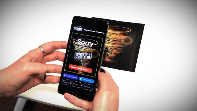 Hand holding a phone using the virtual vortex app and hovering above an image of a vortex