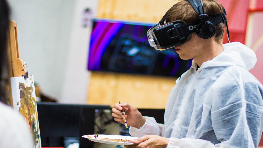 Artist Using VR For Student Education, painting picture on easel with VR headset on