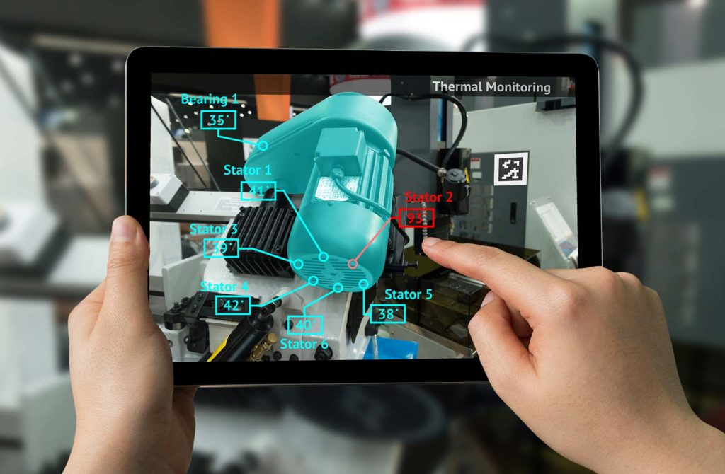 Hands holding an i-pad, augmented reality graphic appearing over an engine on the i-pad