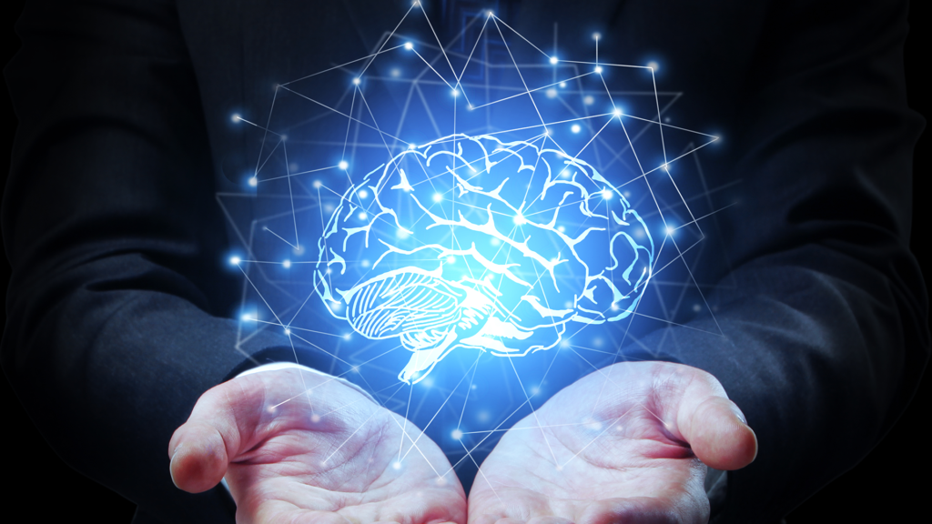 front view of two hands holding a graphic of a glowing brain, floating slightly above the hands while surrounded by a net of glowing dots connected by fine lines
