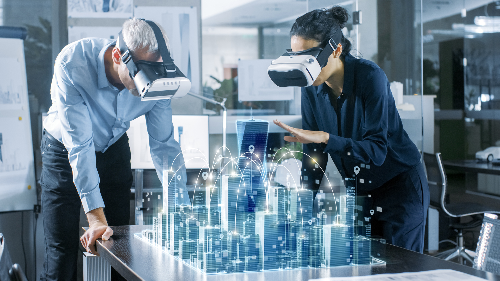 Man and woman in an office environment with VR headsets on bending over a table that has a virtual city scape growing out if it and some graphic arches connecting some buildings.