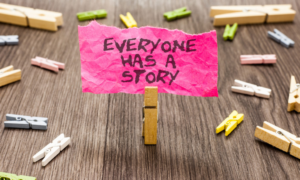 pegs spread out on table, one peg holding holding note saying everyone has a story