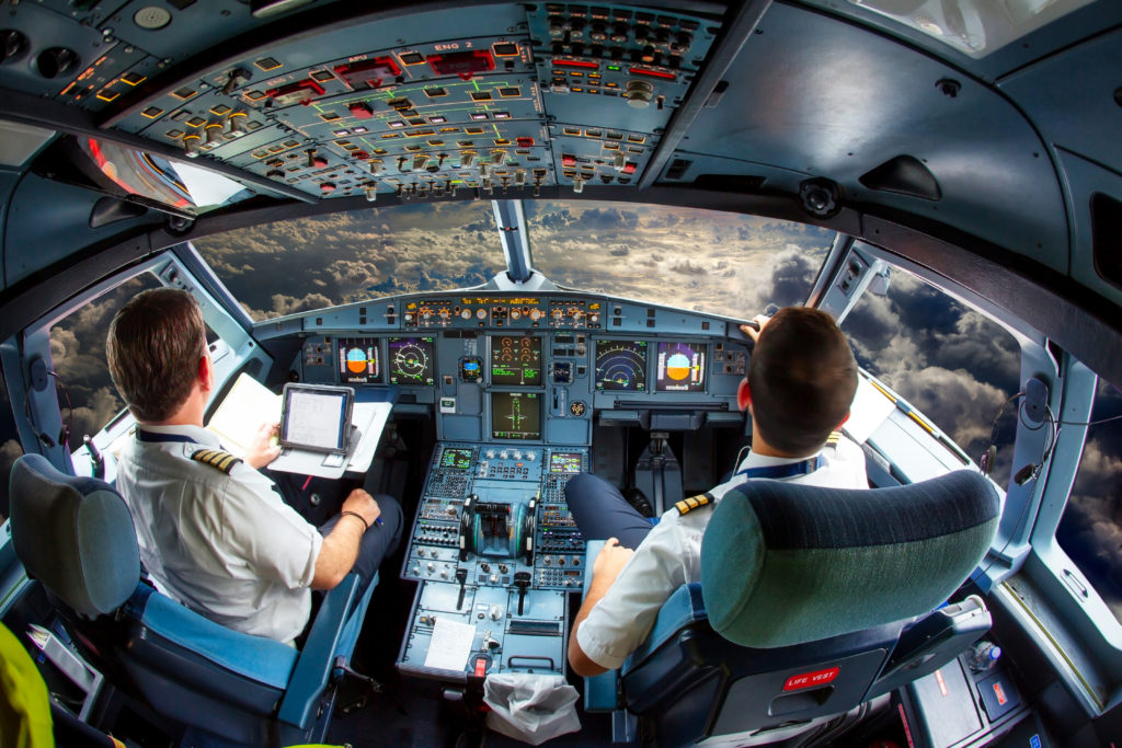 rear view through the cockpit of two pilots flying a plane
