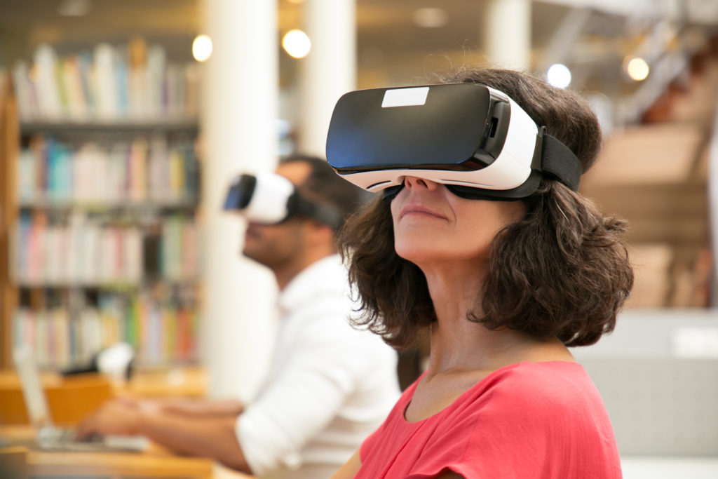 Close up of a woman and man using VR headsets in a library, the woman is in the foreground in focus