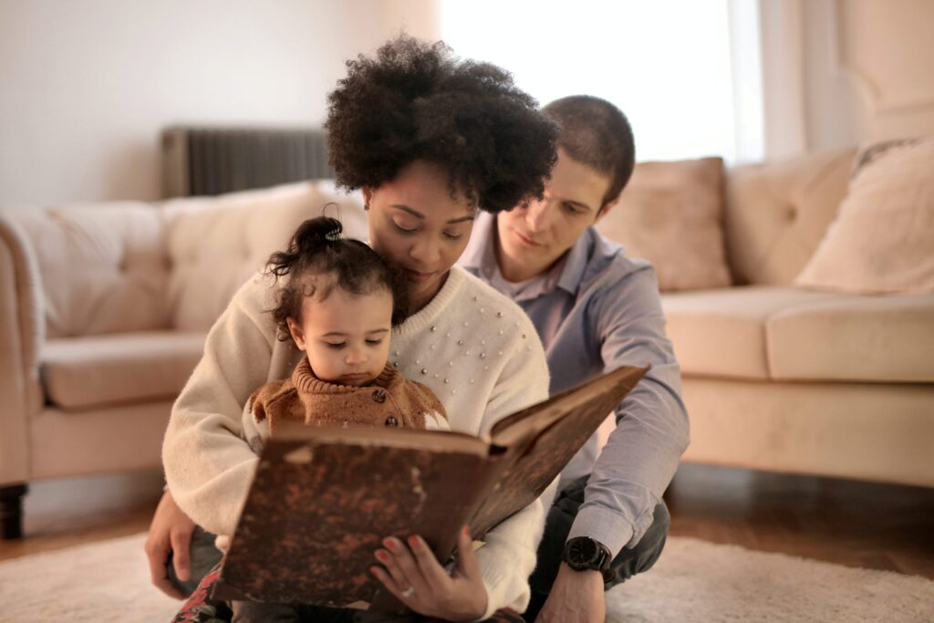child sat on mother's lap while she holds the book reading, dad sits behind, all say on living room rug with sofa and arm chair in background