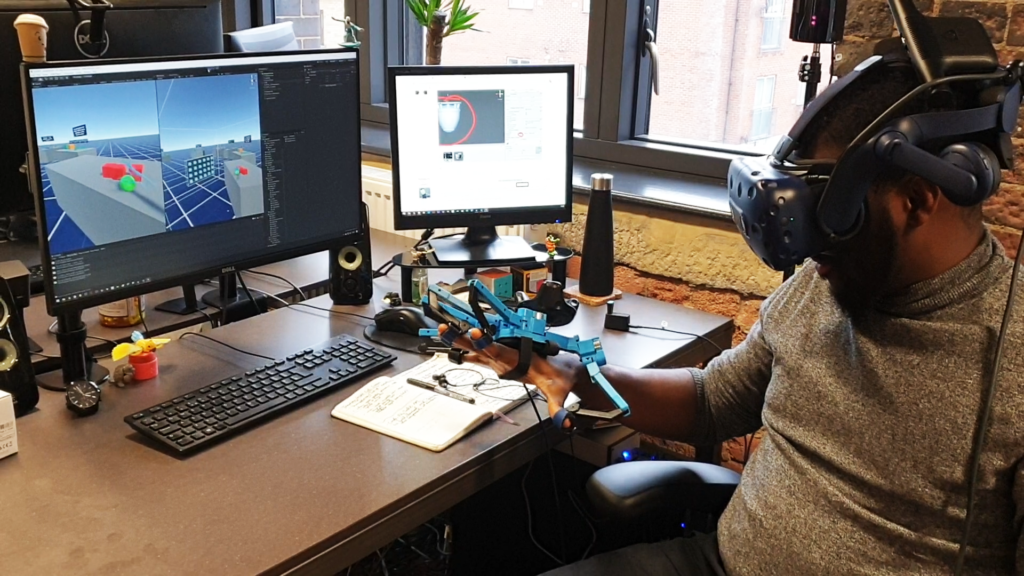 Desktop screen showing Unity interface linked up to a person wearing a virtual reality headset and haptic glove.