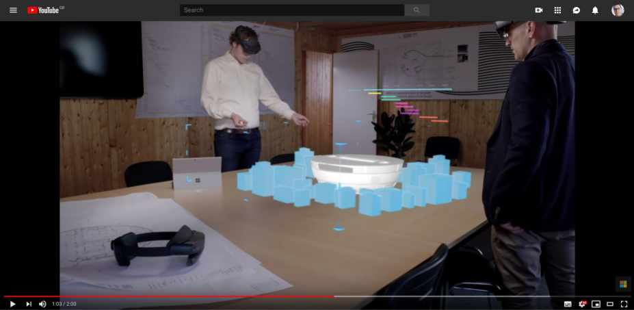 two men standing either side of a table with hololens headsets on looking at an augmented reality construction of a building