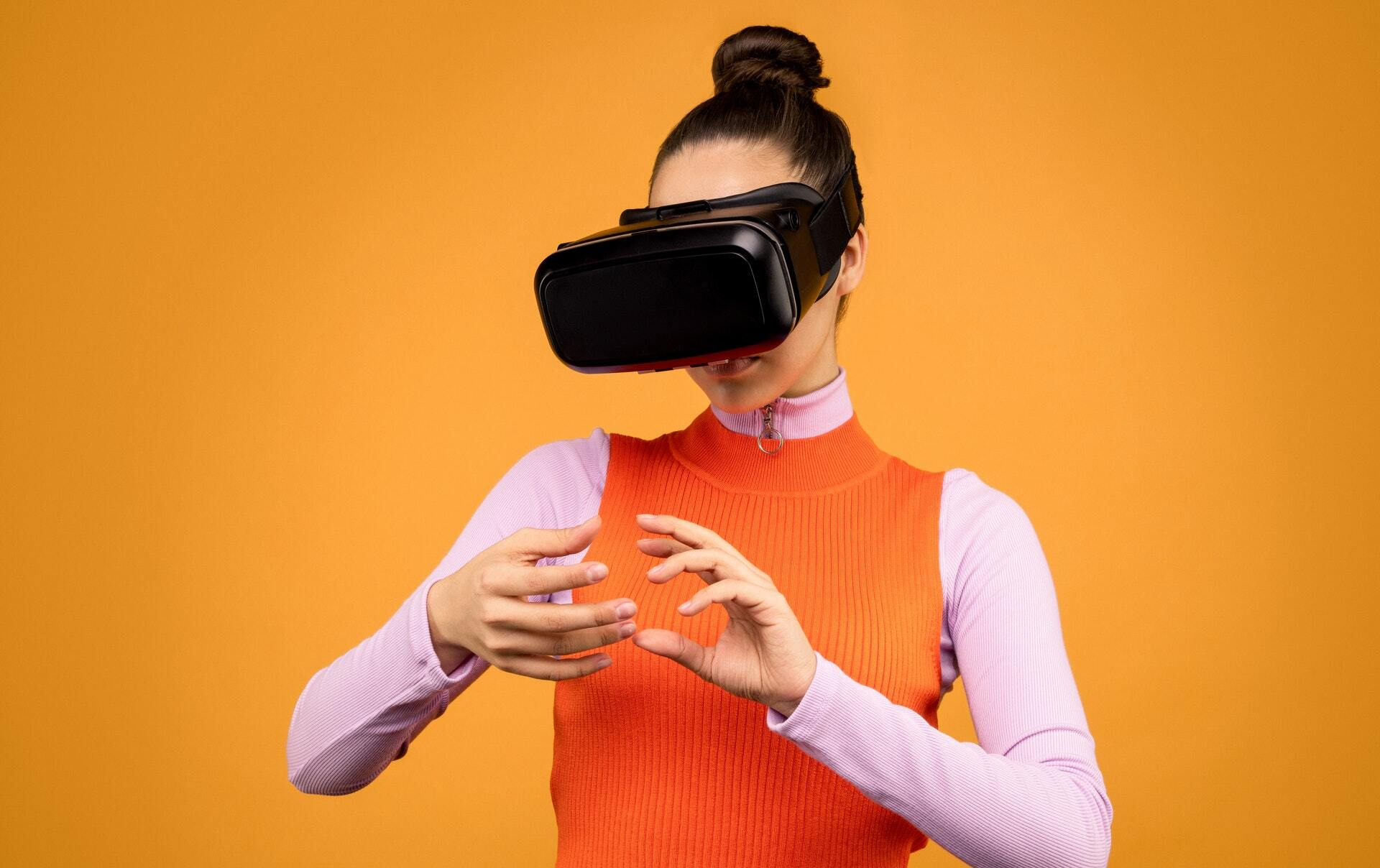 lady in orange tank-top and a vr headset hand tracking